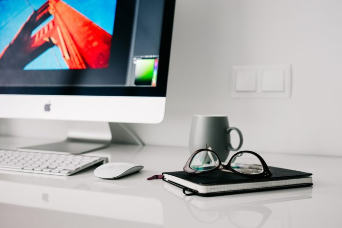 A photo of glasses placed on a journal along with a Mug and an iMac