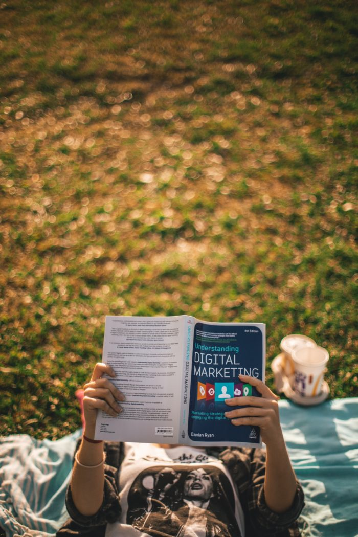 a girl reading digital marketing related book laying on the grass