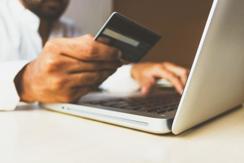 A person using a credit or debit card for online shopping